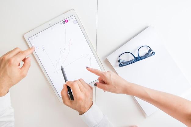 Dois jogadores de negócios apontando para tablet digital gráfico com gráfico desenhado na tela