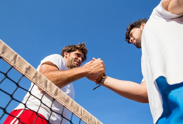 Dois jogadores de tênis profissionais segurando mãos rede de tênis após partida.