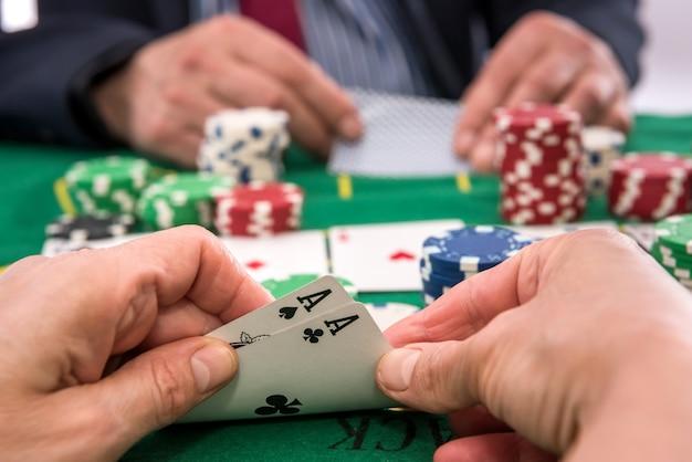 Dois jogadores jogando fichas de pôquer e cartas ou blackjack no cassino