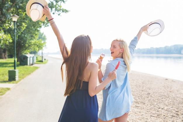 Dois, jovem, amigo feminino, segurando, chapéu, desfrutando, sorvete, em, praia