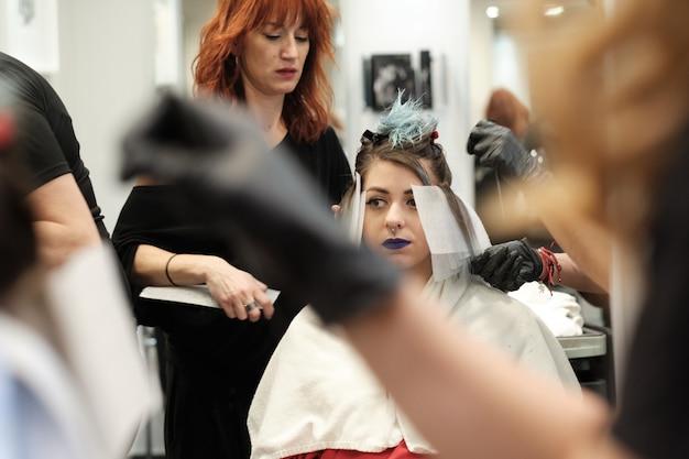 Dois, jovem, cabeleireira, tintura, cabelo, de, femininas, cliente, enquanto, ela, sentar-se cadeira