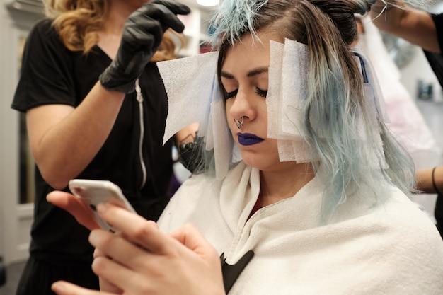 Dois jovem cabeleireiro tingir o cabelo do cliente do sexo feminino enquanto lê seu celular