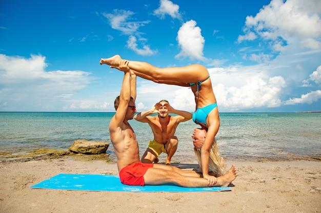 Dois jovem e mulher na praia fazendo exercícios de ioga fitness juntos. elemento acroyoga para força e equilíbrio