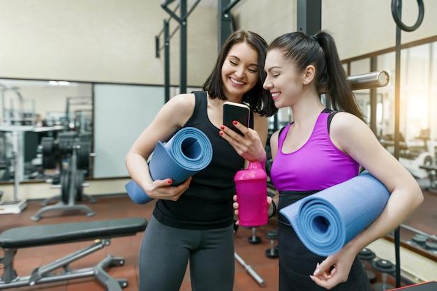 Dois, jovem, esportes, mulheres ginásio, sorrindo, com, condicão física, tapetes