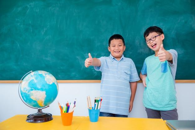 Dois, jovem, estudante asiático, ficar, e, sorrindo, frente, chalkboard, em, escola