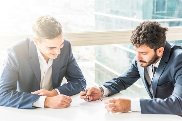 Dois, jovem, homem negócios, planejando, a, plano negócio, branco, escrivaninha