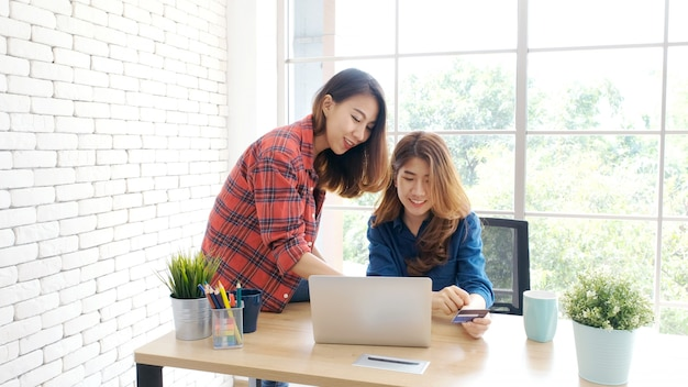 Dois, jovem, mulheres asian, segurando, cartão crédito, e, usando, computador laptop, para, shopping linha, com, felicidade