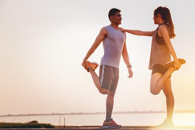 Dois, jovem, pares, atletas, worming, cima, para, ao ar livre, prática, com, pôr do sol, fundo