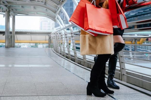 Dois jovem segurando muitas sacolas vermelhas coloridas