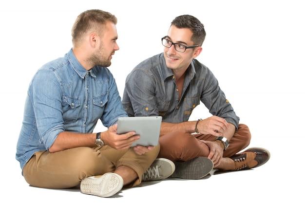 Dois jovem sentado no chão, conversando