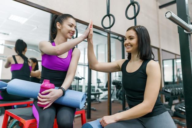 Dois, jovem, sorrindo, condicão física, mulheres conversando, com, tapetes esporte