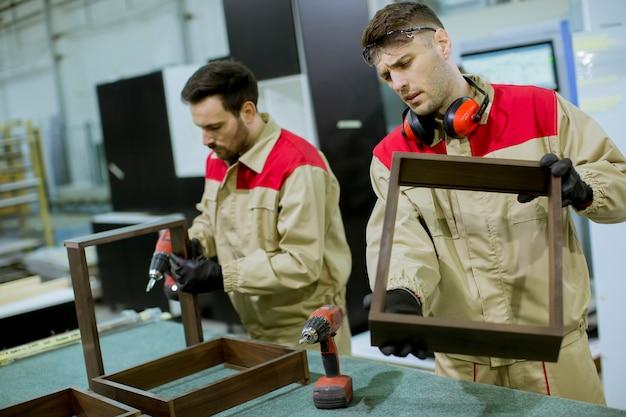 Dois, jovem, trabalhadores, montagem, mobília, em, a, fábrica