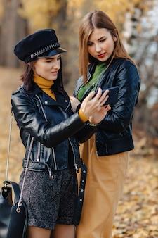 Dois jovens acolhedores andar no outono park road fazer fotos