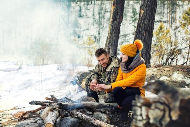 Dois jovens adultos do sexo masculino e feminino ficam felizes em sentar-se juntos no inverno ao redor da fogueira