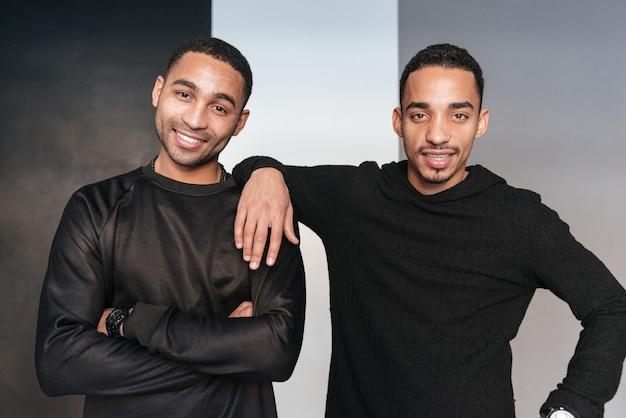 Dois jovens afro-americanos felizes em pé com os braços cruzados