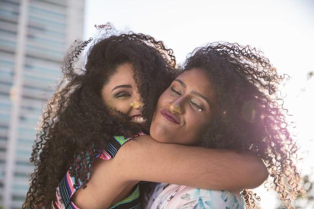Dois jovens afro meninas se divertindo juntos, alegria, positivo, amor, amizade, irmãs.