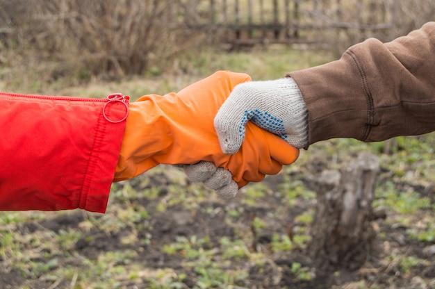 Dois jovens agricultores apertam as mãos sobre o fundo do solo na primavera