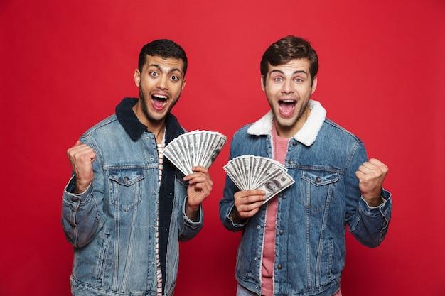 Dois jovens alegres, isolados sobre a parede vermelha, segurando notas de dinheiro, comemorando