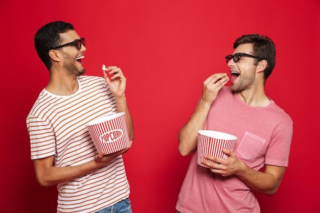 Dois jovens alegres, isolados sobre uma parede vermelha, comendo pipoca e usando óculos 3d