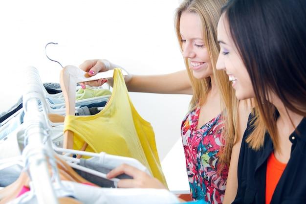 Dois jovens amigos à procura de roupas na loja