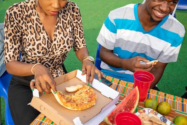 Dois jovens amigos africanos comendo pizza