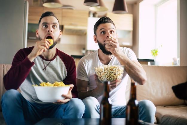 Dois jovens amigos barbudos felizes assistindo tv ou alguma partida de esporte enquanto estão sentados no sofá em casa no fim de semana, bebendo cerveja e comendo lanches