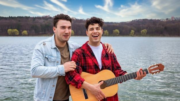 Dois jovens amigos cantando e tocando violão perto de um lago em um parque