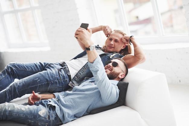 Dois jovens amigos elegantes deitados no sofá e tirando uma selfie