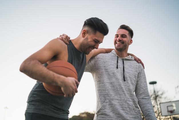 Dois jovens amigos jogando basquete.