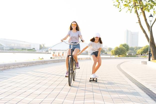 Dois jovens amigos relaxando em um dia quente de verão com uma jovem andando de bicicleta e rebocando a amiga de skate em uma rua urbana.