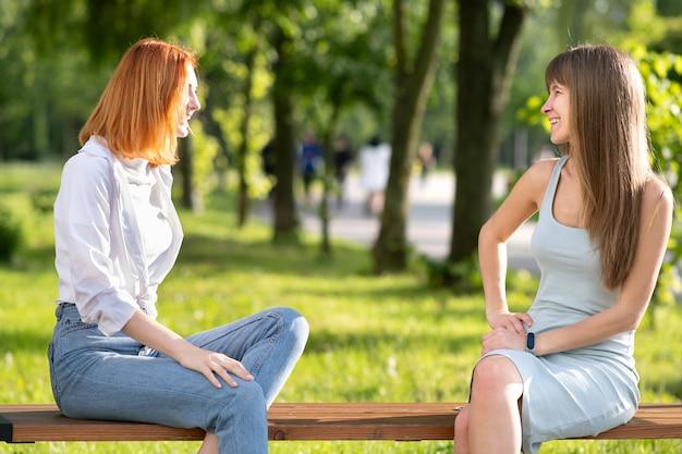 Dois jovens amigos, sentado em um banco no parque de verão conversando alegremente