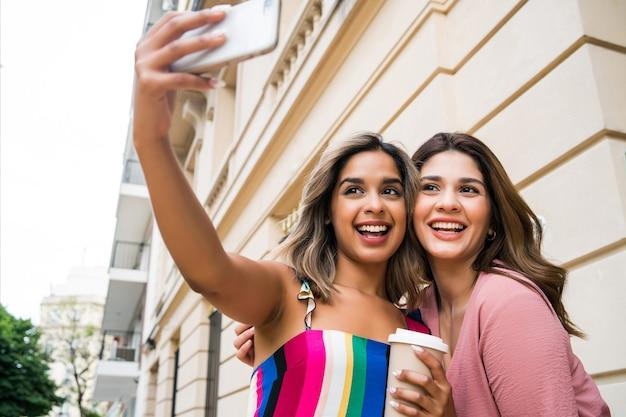 Dois jovens amigos sorrindo e tirando uma selfie com o celular ao ar livre