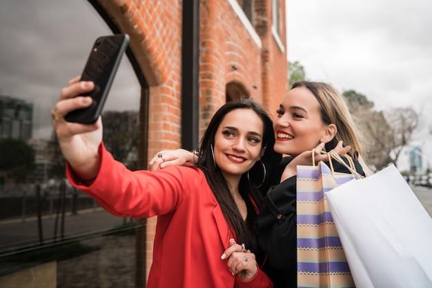 Dois jovens amigos tomando uma selfie com telefone móvel.