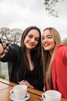 Dois jovens amigos tomando uma selfie juntos na cafeteria.