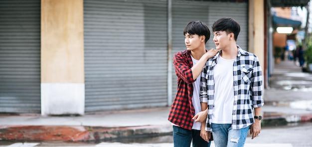 Dois jovens amorosos em camisas e andando na rua.