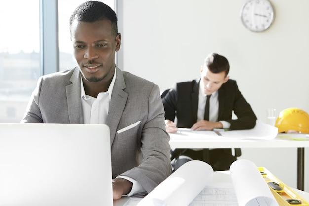 Dois jovens arquitetos da empresa de engenharia trabalhando no escritório. designer africano desenvolvendo novo projeto de construção usando laptop, sentado à mesa com rolos e régua.