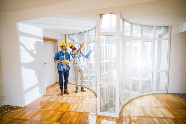 Dois jovens arquitetos do sexo masculino andando por um apartamento vazio, conversando sobre algumas mudanças.
