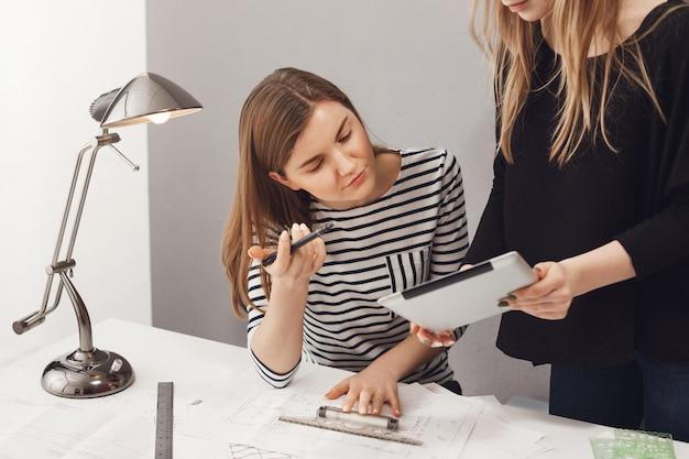 Dois jovens arquitetos femininos freelancers bem sucedidos olhando através do plano de trabalho, falando sobre prazos, fazendo plantas para o cliente. conceito de freelance, negócios e trabalho em equipe.