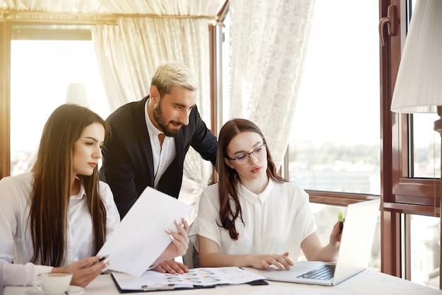 Dois jovens assistentes e um diretor estão discutindo o andamento do trabalho do restaurante