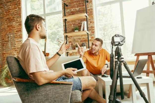 Dois jovens blogueiros caucasianos com roupas casuais e equipamento profissional