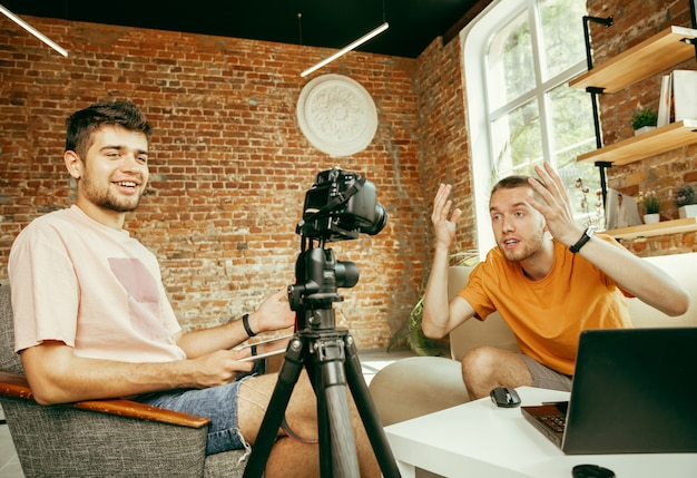 Dois jovens blogueiros do sexo masculino, caucasianos, com roupas casuais, equipamento profissional ou uma câmera gravando uma entrevista em casa
