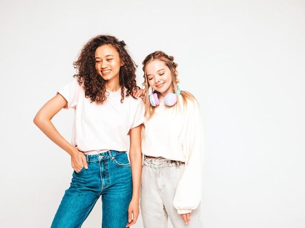 Dois jovens bonitos sorrindo hipster internacional feminino em roupas da moda de verão. mulheres despreocupadas posando em estúdio