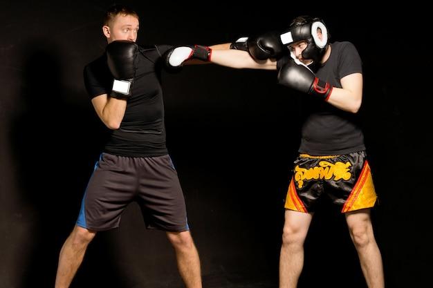 Dois jovens boxeadores musculosos em boa forma lutando no ringue