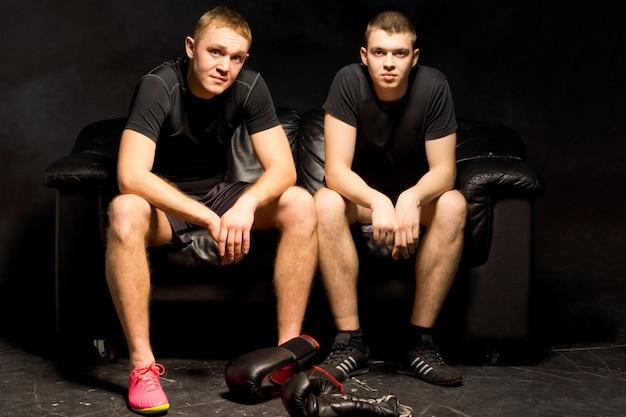 Dois jovens boxeadores relaxam antes de uma sessão de treinamento