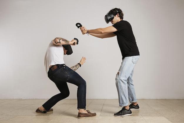 Dois jovens brigam com fones de ouvido de rv, o homem de camiseta preta bate e o homem de camiseta branca se afasta
