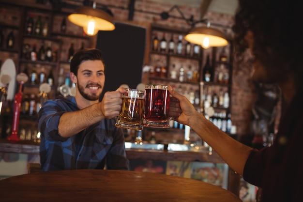 Dois jovens brindando suas canecas de cerveja