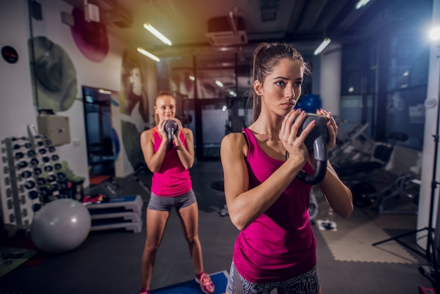 Dois jovens cabem meninas malhando em uma academia. de pé no stepper e fazendo agachamentos, mantendo pesos nas mãos.