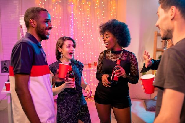 Dois jovens casais interculturais alegres em trajes glamorosos tomando drinques em uma festa em casa e discutindo coisas engraçadas
