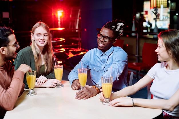 Dois jovens casais interculturais em trajes casuais tomando suco de laranja enquanto estão sentados à mesa em um café depois de jogar boliche e bater um papo