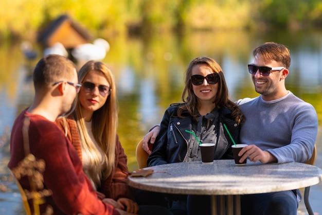 Dois jovens casais tomando drinques ao ar livre, sentados à mesa em um restaurante com vista para um lago, aproveitando o sol de outono